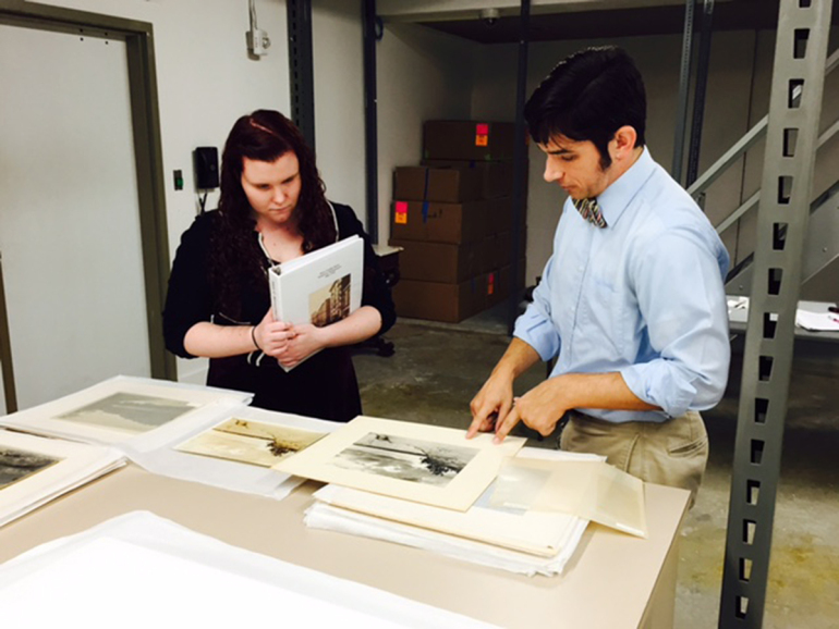 PRINTS IN PROGRESS: As part of her internship with the Chrysler Museum, Stephanie Deach '17 worked alongside Brock Curator of American Art Alex Mann to evaluate and select photographs for the Harry Cowles Mann exhibition. (Photo by Kathleen Casey)
